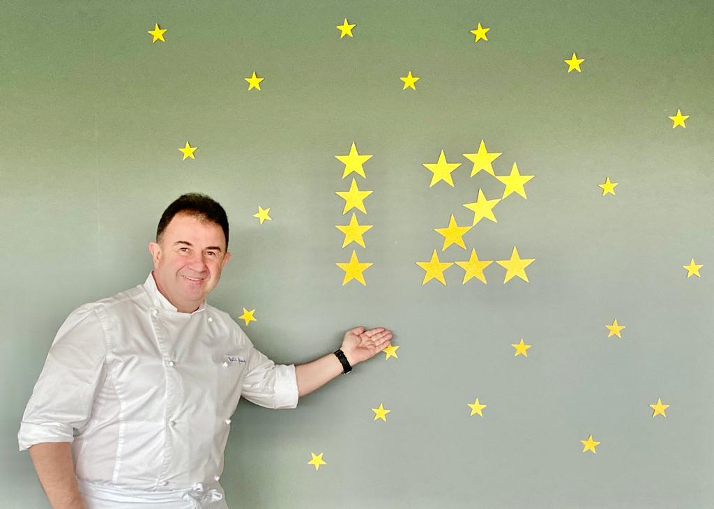 Martin Berasategui fotografiat langa un perete cu 12 stele galbene reprezentand stelele michelin