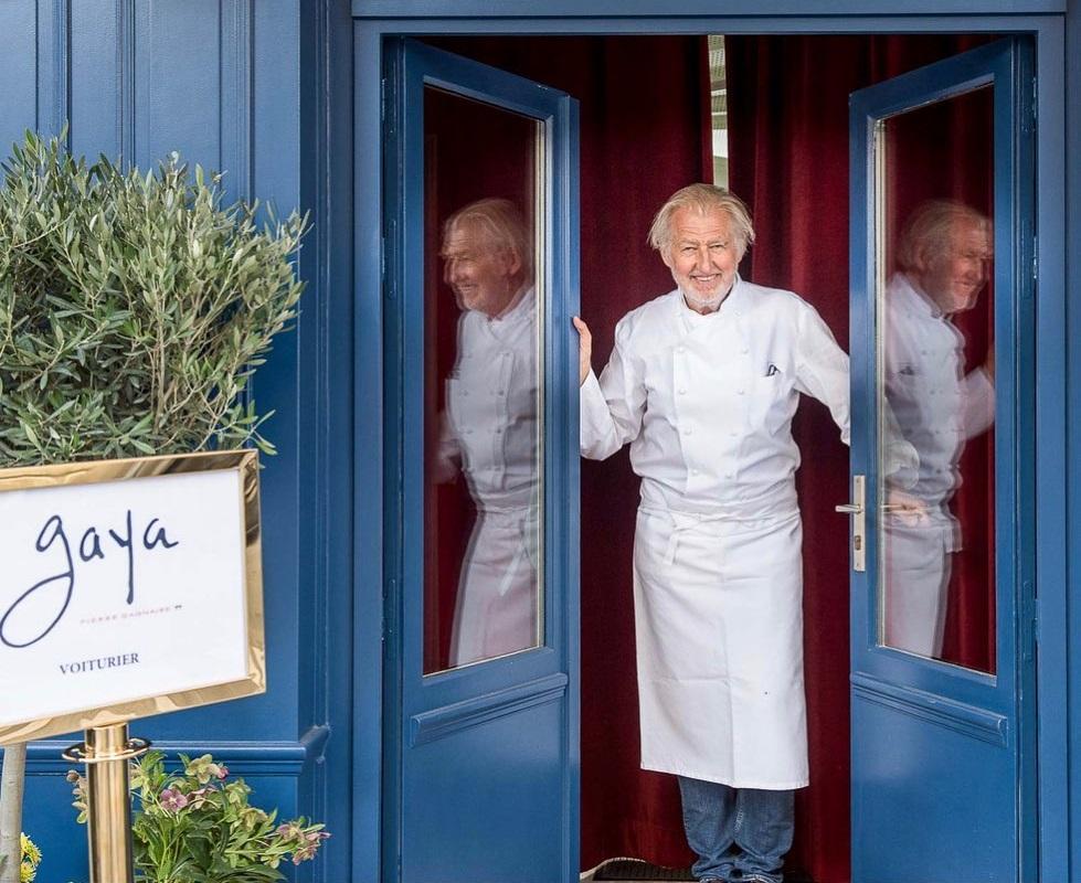 Pierre Gagnaire in uniforma de bucatar, fotografiat in usa restaurantului, cu usi albastre, unul din cei mai buni bucătari din lume