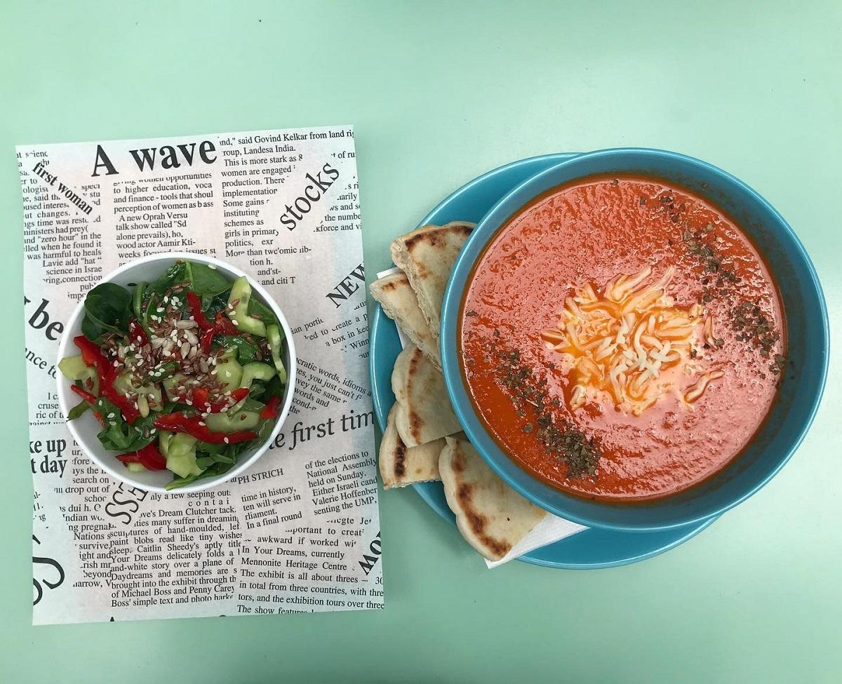 doua boluri cu supa crema si salata, asezate pe ziar, la meniu de pran flip flop bistroteca