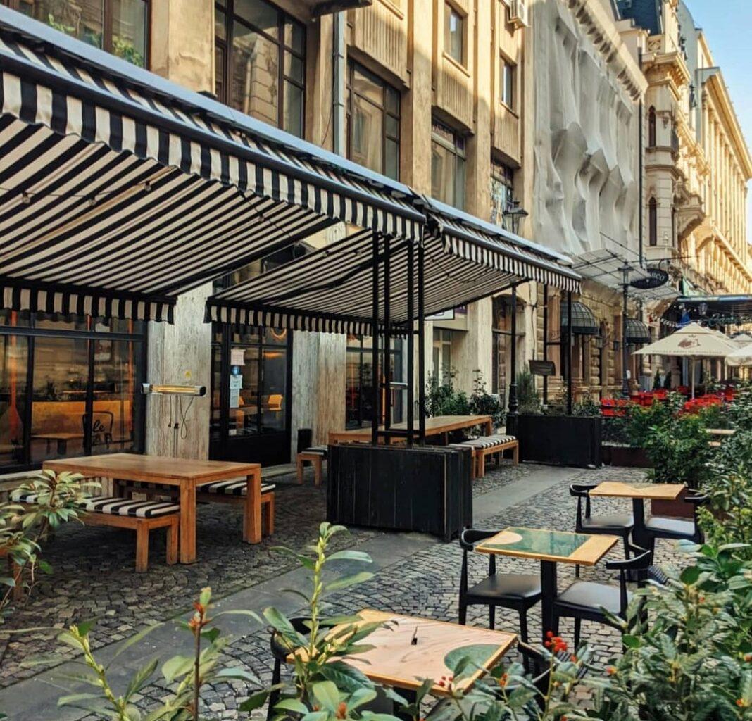 terasa Le Bab, cu mese afara si copertina in dungi alb si negre, una din terase încălzite din București