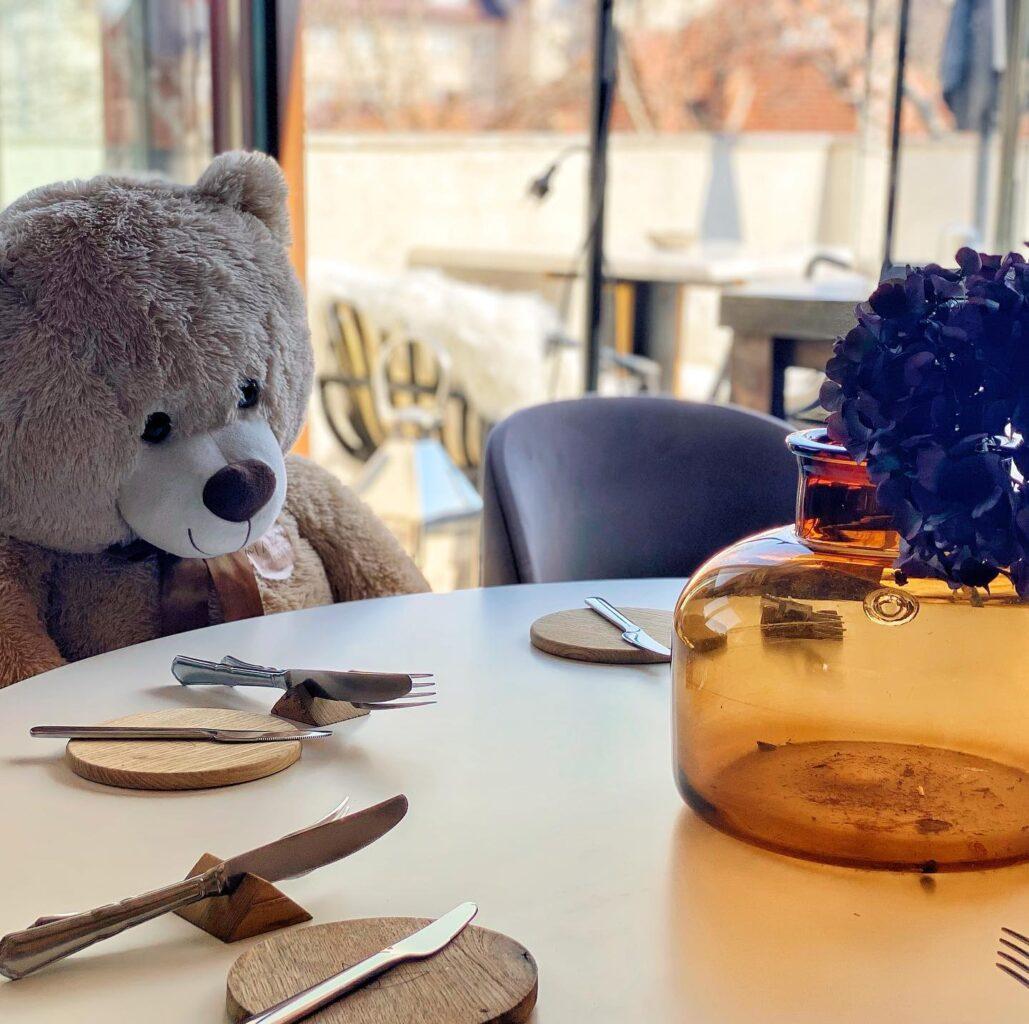 urs de pluș așezat la o masa rotundă de la restaurant Maize farm to table