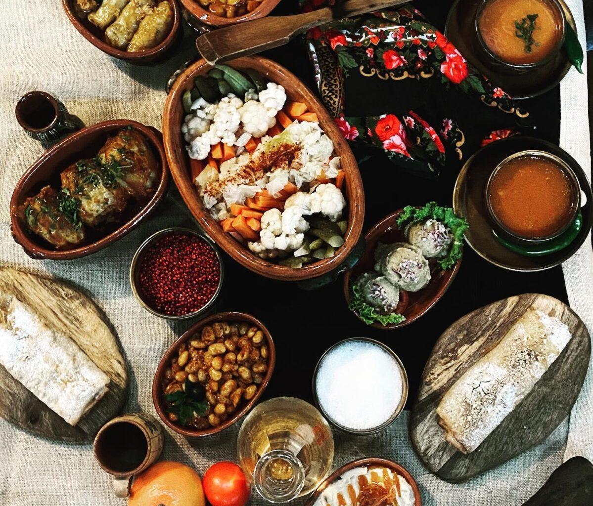Masă plină cu mâncare de post de diverse sortimente, fotografiată de sus, la Taverna Sârbului