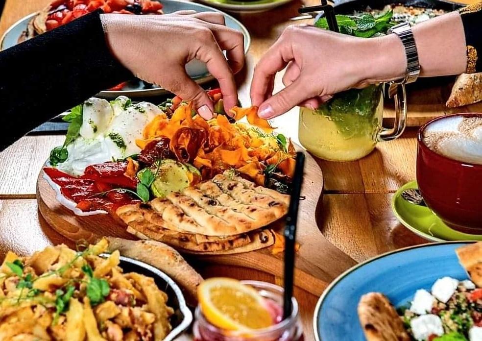 prim plan cu o masa plina de farufurii cu mancare si doua maini care apuca din preparate, meniu de prânz la gram bistro bucurești