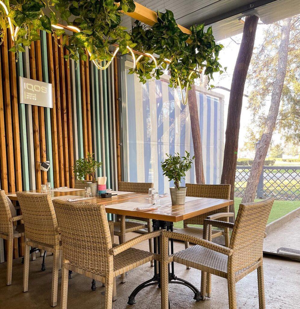 masa cu patru scaune din lemn, cu un corp de iluminat cu plante deasupra, la stadio park, una din terase încălzite din București