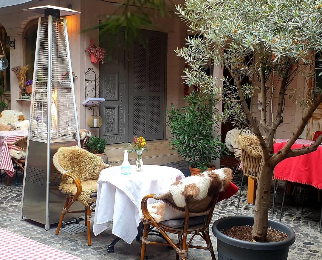 masa rotunda cu doua scaune invelite in blanuri, si un incalztior de terasa langa, la restaurant White Horse Restaurant & Pub