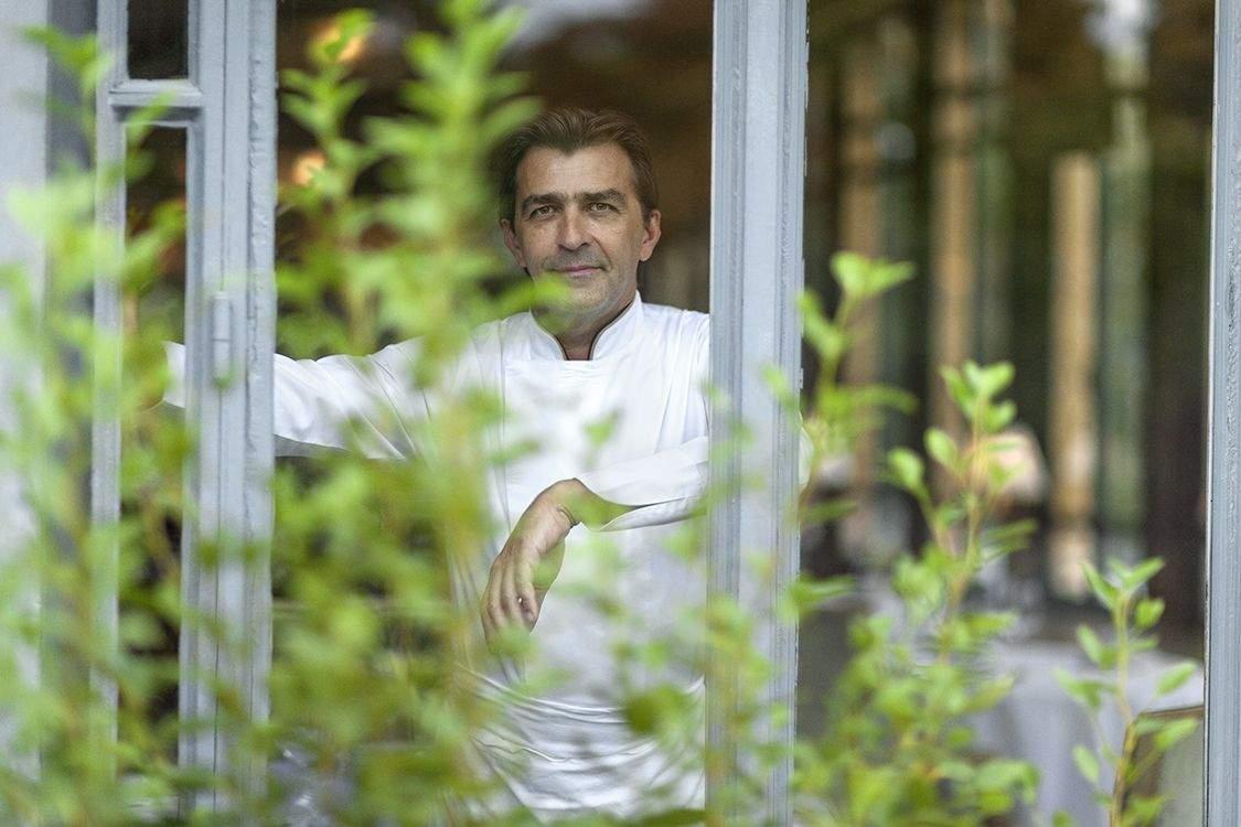 Yannick Alleno in uniforma de bucatar, fotografiat in dreptul unei ferestre, printre plante, unul din cei mai buni bucătari din lume