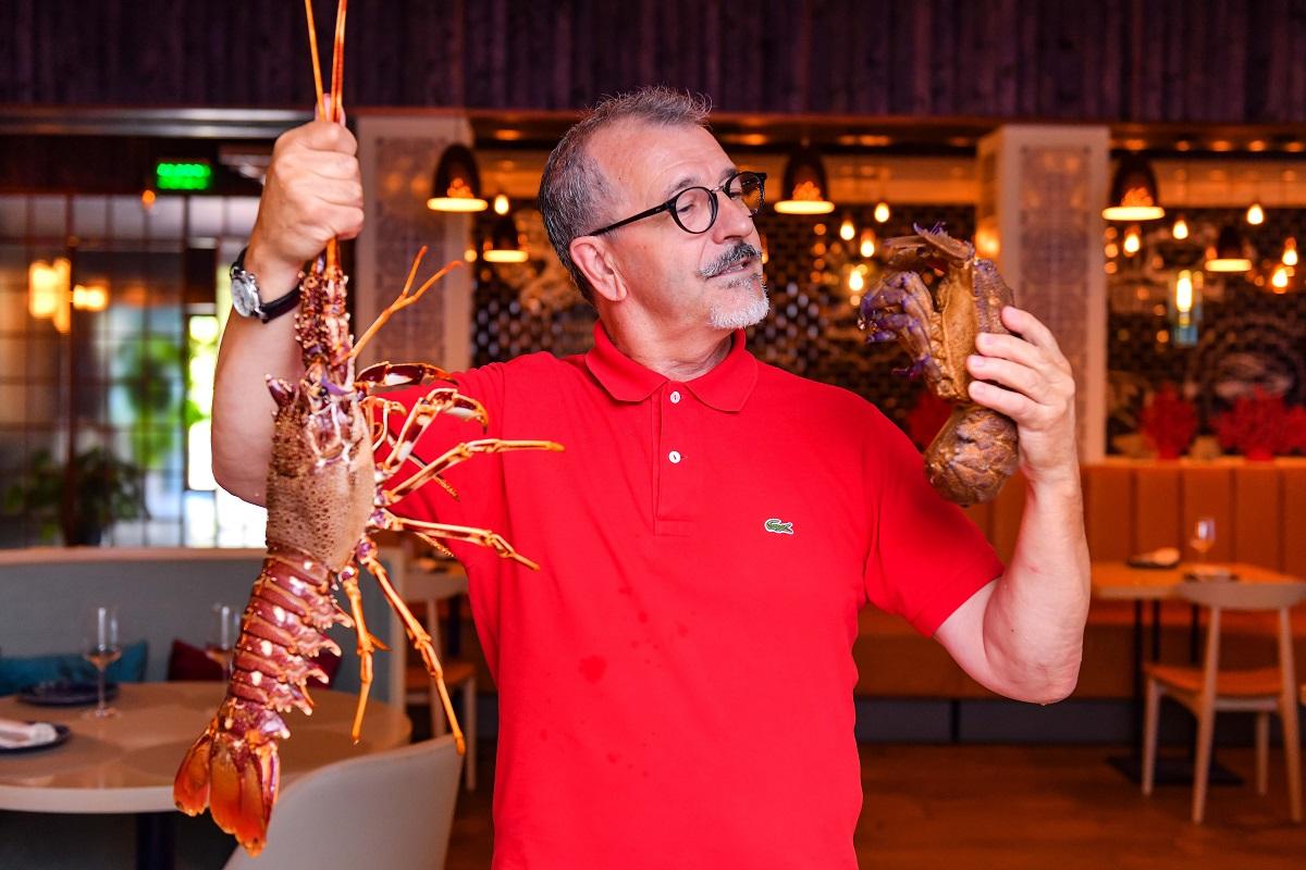 Jose Gaspar, proprietarul restaurantului Dancing Lobster, imbracat in tricou rosu, tinand in maini un homar foarte mare