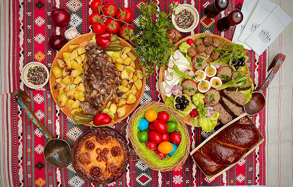 masă tradițională de Paște disponibilă la comandă la Restaurant Vatra, cu ouă vopsite in diverse culori, pasca, platou rece cu carne, oua, legume, branza, friptura de miel cu cartofi, pe stergar cu motive traditionale