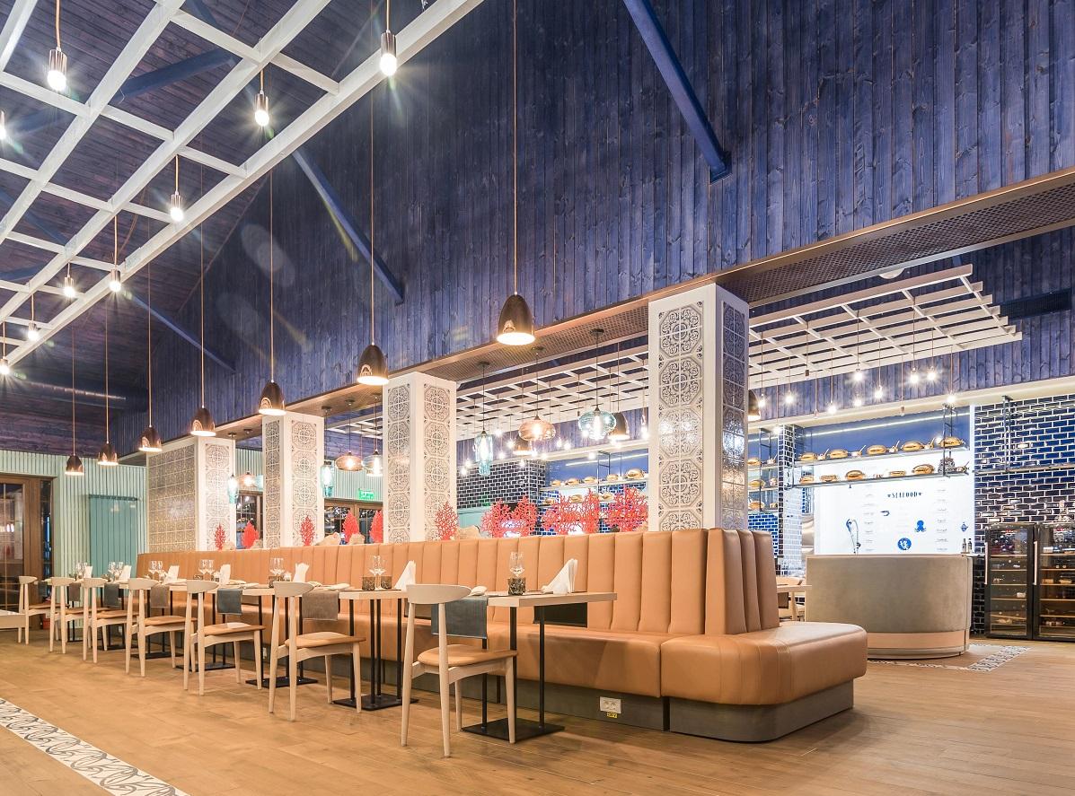 imagine de ansamblu din interiorul restaurantului Dancing Lobster, cu un sir de mese in fata unei canapele, vitrine cu peste in spate si pereti albastri