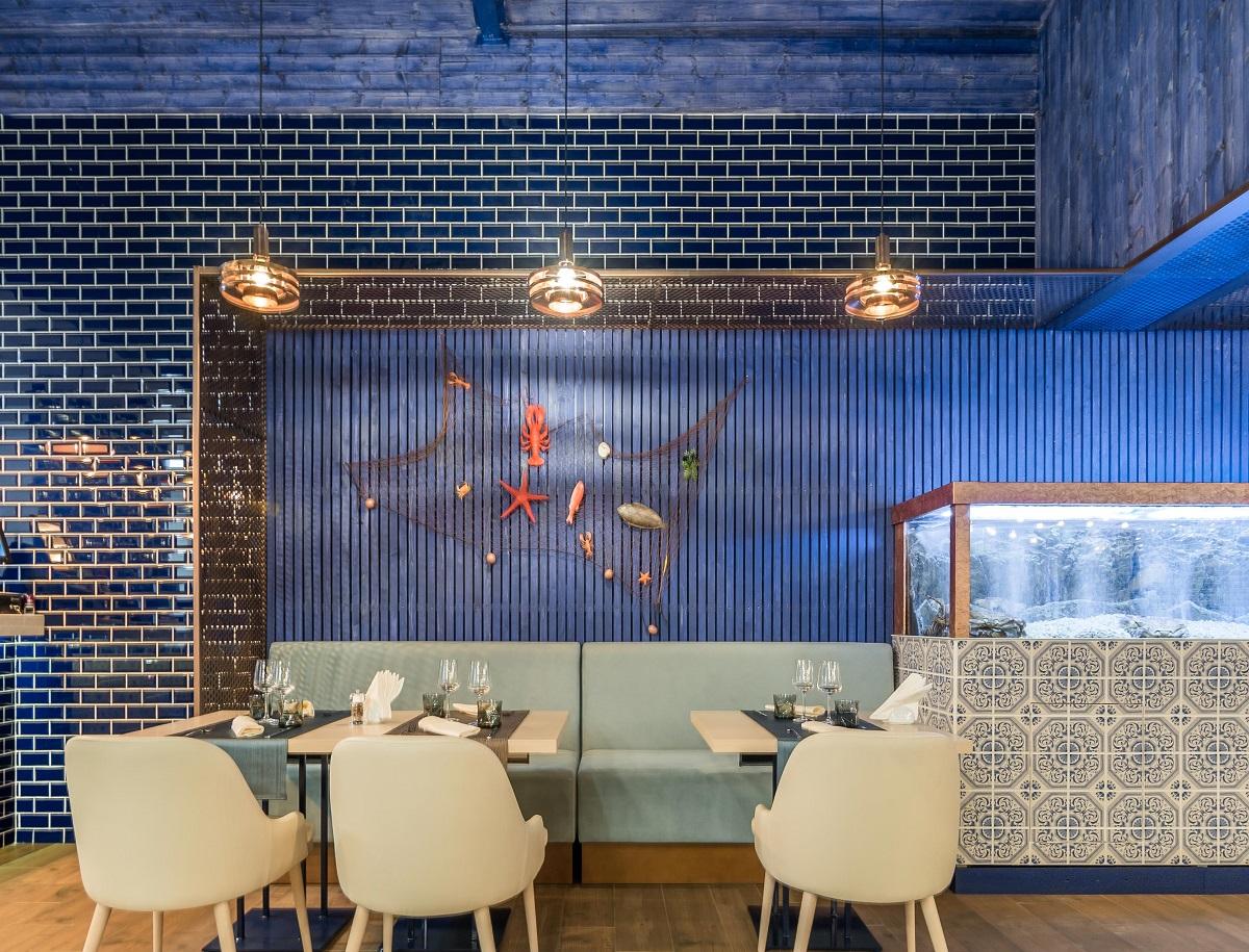 masa de la restaurant Dancing Lobster din Bucuresti cu scaune crem, in fata unui perete albastru