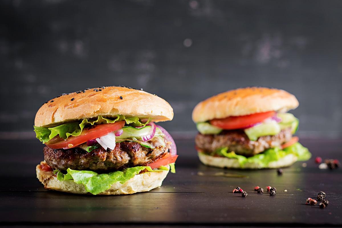 doi burgeri cu chifla cu seminte, rosii, ceapa, carne plant-based si salata, fotorafiata pe fundal negru