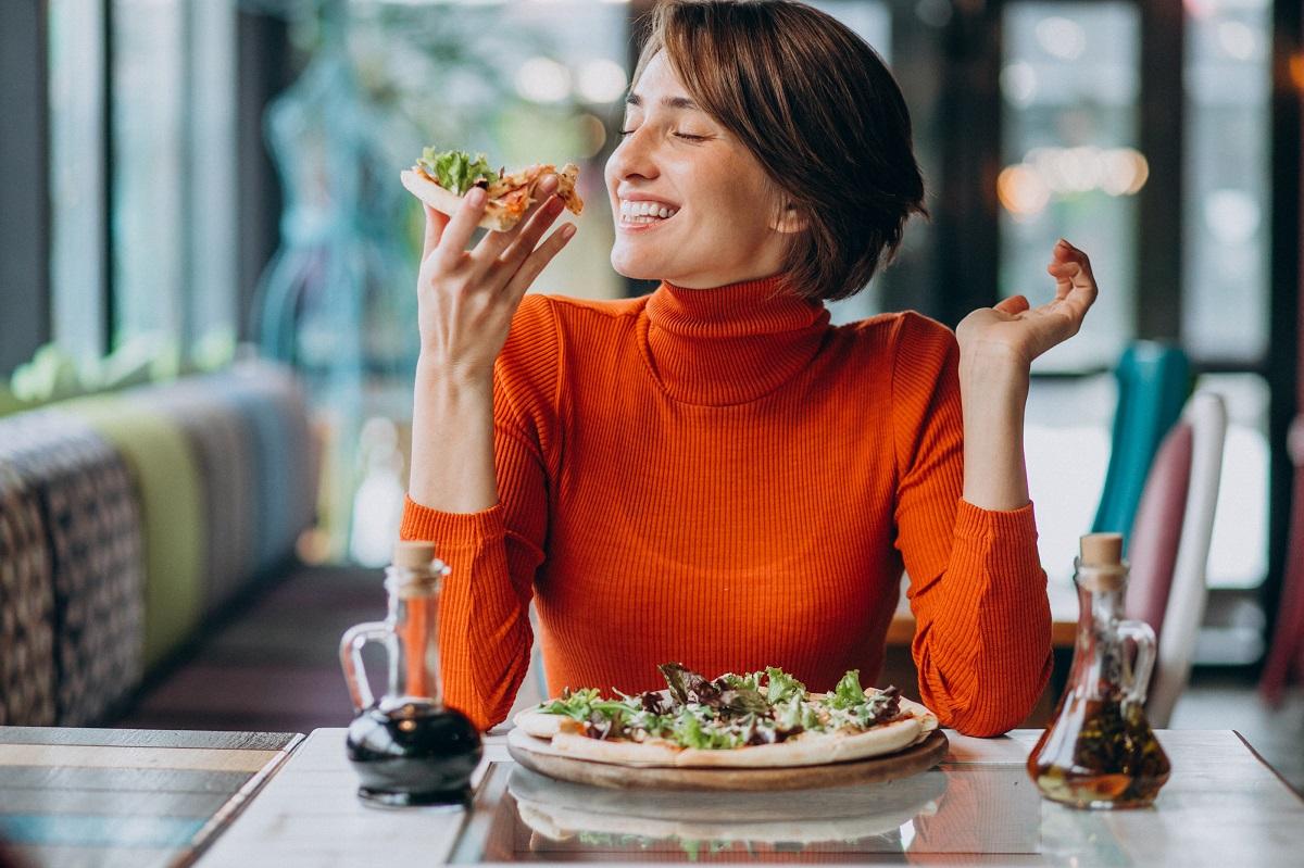 Femeie tanara care mananca pizza la restaurant, imagine reprezentativa pentru echilibrul nutrițional din farfurie