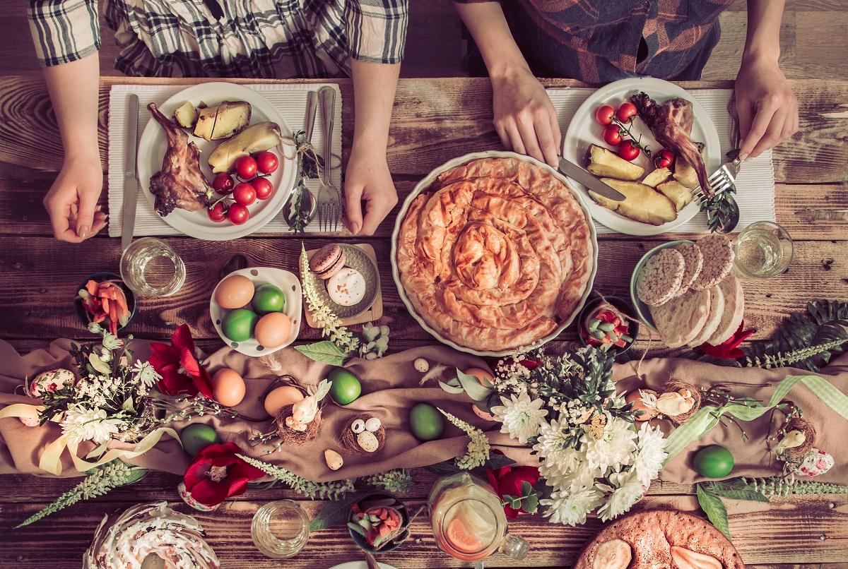 masa de paste fotografiata de sus, cu oua rosii, pasca, farfurii cu mancare, friptura de mie, ca exemplu de excese alimentare