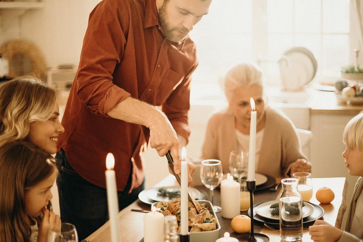 familie la masa de paste, in jurul caruia stau o femeie, un copil, o batrana si un barbat in picioare care taie cu  cutitul friptura, pe masa sunt lumanari