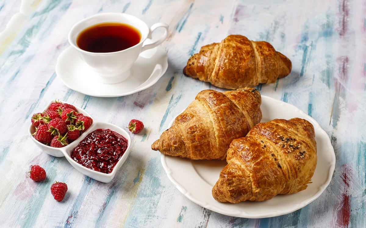 mic dejun franțuzesc cu croissante, gem de zmeură, zmeură proaspătă și o ceașcă de cafea