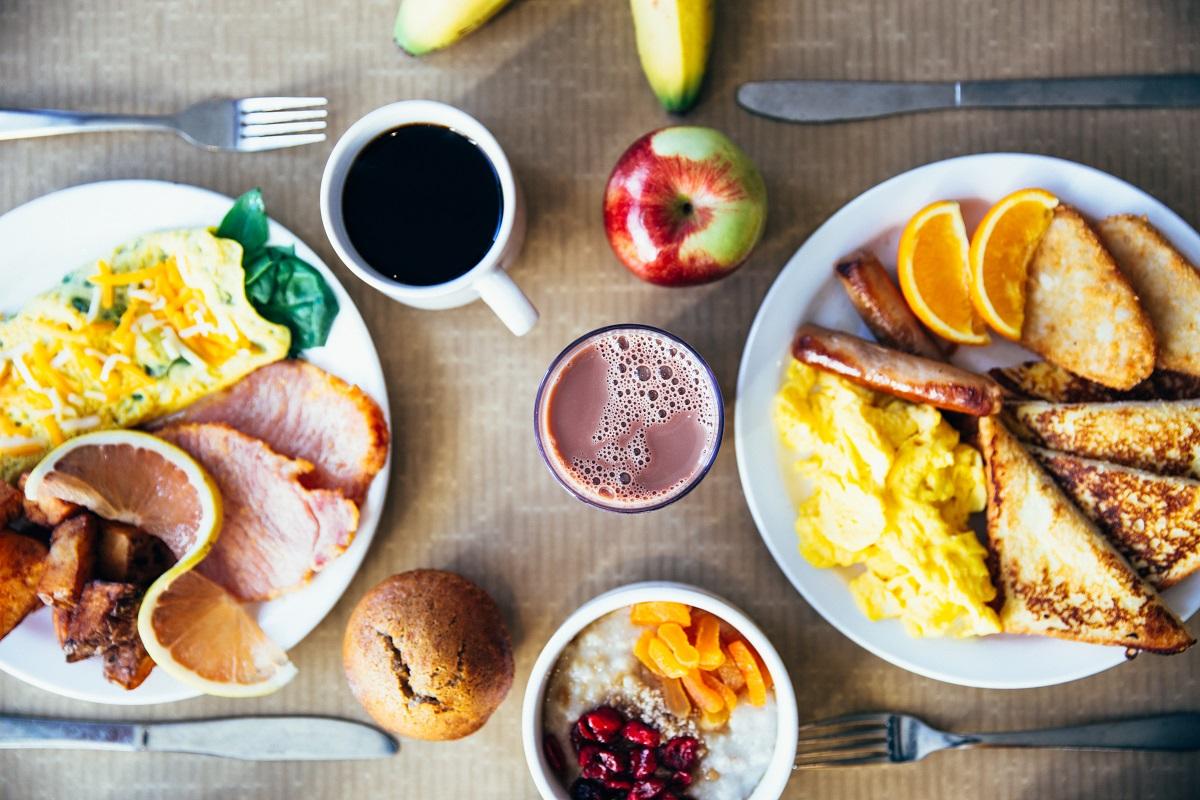 masa de mic dejun cu doua farfurii fotografiate de sus cu omleta, bacon, cereale cu lapte si fructe, un mar si cafea