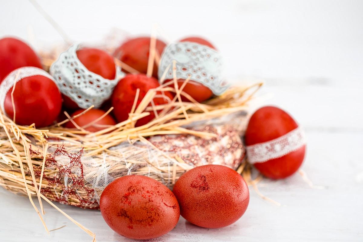 Ouă roșii într-un coș cu paie, legate cu panglică de dantelă, fotografiate de aproape, pentru comandă masa de Paște