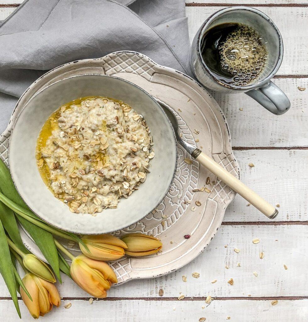 Hafragrautur sau un fel de porridge, intr-o farfurie eleganta, cu o cana de cafea si lalele galbene langa