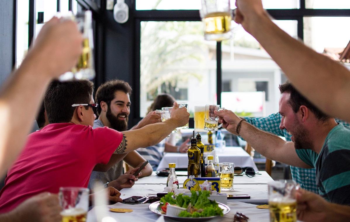 grup de barbati care ciocnesc halbe de bere la un restaurant ca imagine descriptiva pentru masuri de relaxare 15 mai