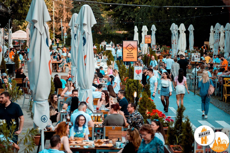 terasa foarte mare, plina cu oameni asezati la mese, cu umbrele stranse, la Berăria H din București