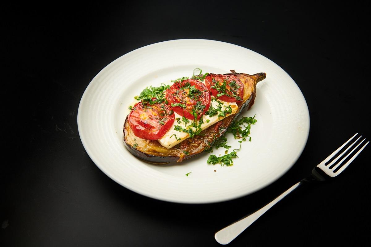 Papoutzakia, vinete umplute cu carne tocată și legume, pe farfurie alba si fundal negru, de la Amvrosia restaurant. Un preparat din cele ce să mănânci în Grecia