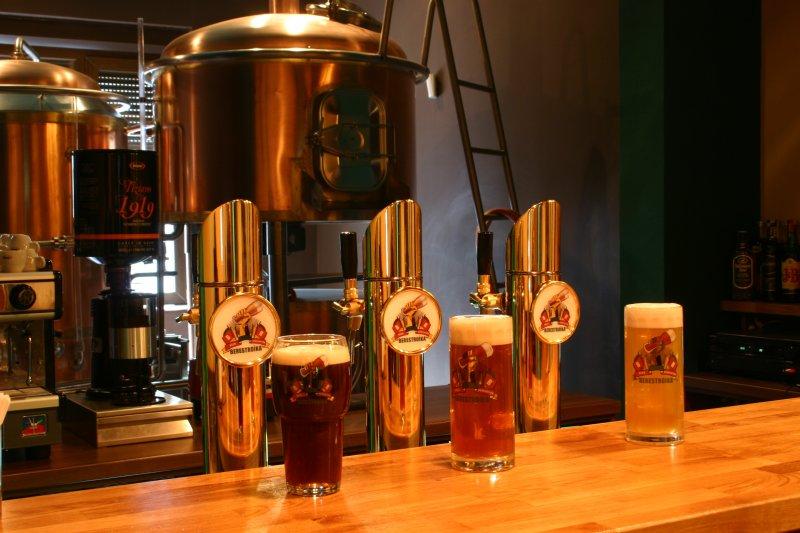 trei halbe de bere, blonda, bruna si roscata, in fata unor dozatoare, cu un tanc d ebere in spate la Berestroika Beer Revolution din București