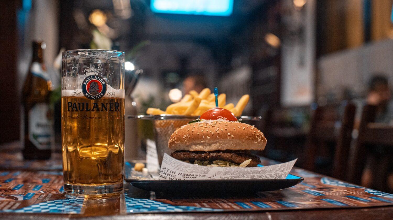 o halba de bere plina, asezata pe bar, langa o farfurie cu burger si cartofi prajiti la Bierhaus 67 din București