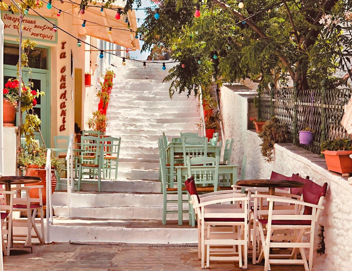 taverna din Grecia cu mese colorate asezate pe niste trepte albe si copaci in jur