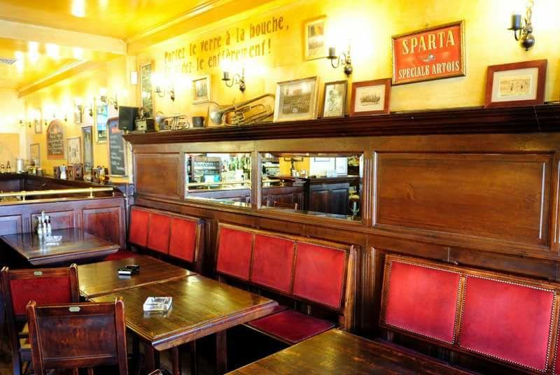 restaurantul la Belle Epoque, cu mese patrate din lemn si canapele rosii, cu multe fotografii pe pereti
