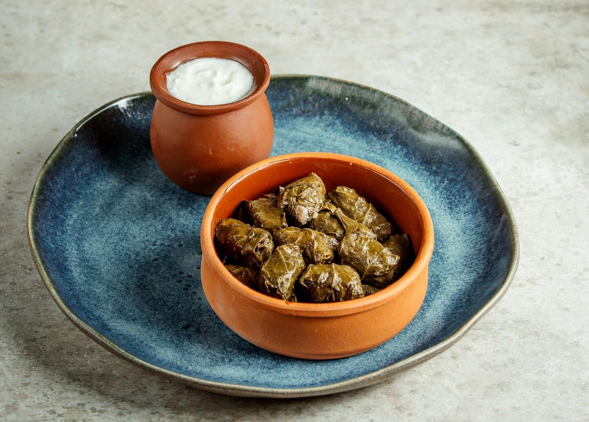 Sărmăluțe Dolmadakia, in bol de lut, cu sos de iaurt, pe o farfurie albastra. Un preparat din cele ce să mănânci în Grecia