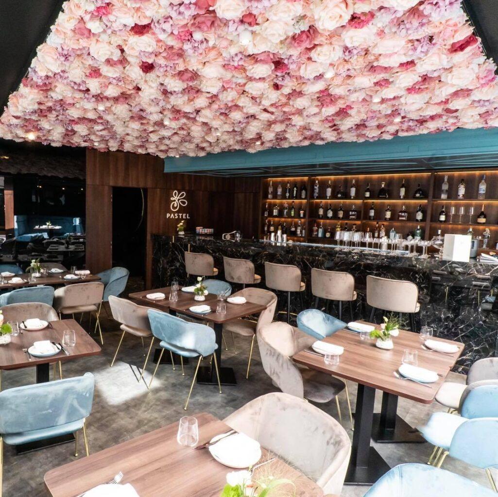 restaurantul pastel din cluj, cu mese din lemn, scaune crem si albastre si tavan cu flori roz