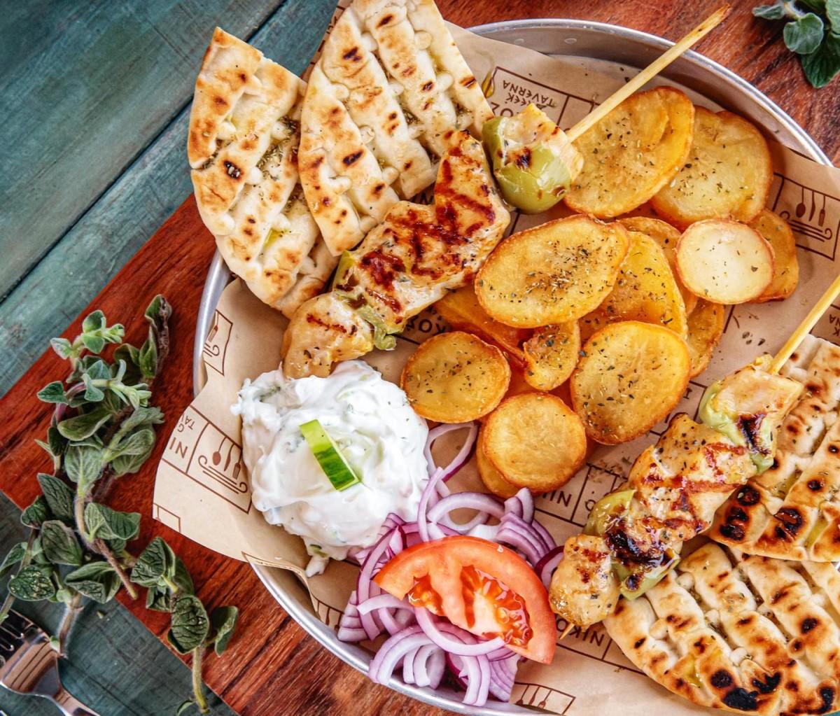 Souvlaki cu pita, cartofi prajiti taiati rondele, frigarui de pui, sos, rosii si ceapa, de la Nikos Greek Taverna din București
