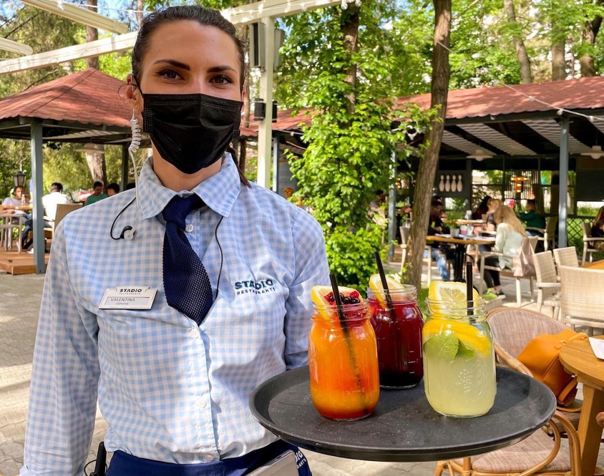 Ospatarita in uniforma cu cravata care tine intr-o mana o tava cu trei carafe mici de limonada, galbena, rosie si portocalie, la Stadio Park Bucuresti
