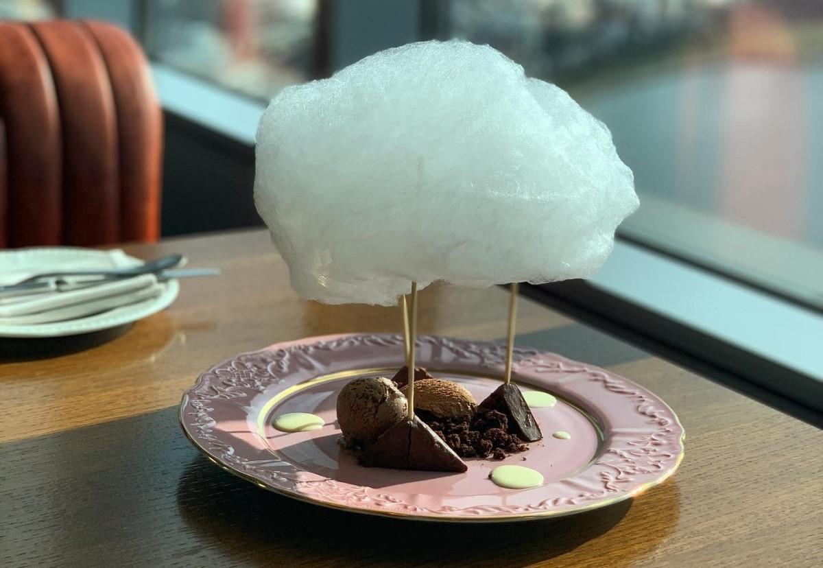 Prăjitură cu ciocolată Nor desupra unui cuib de ciocolată cu trei texturi de ciocolată sub un nor din vată de zahăr, la restaurant NOR din București