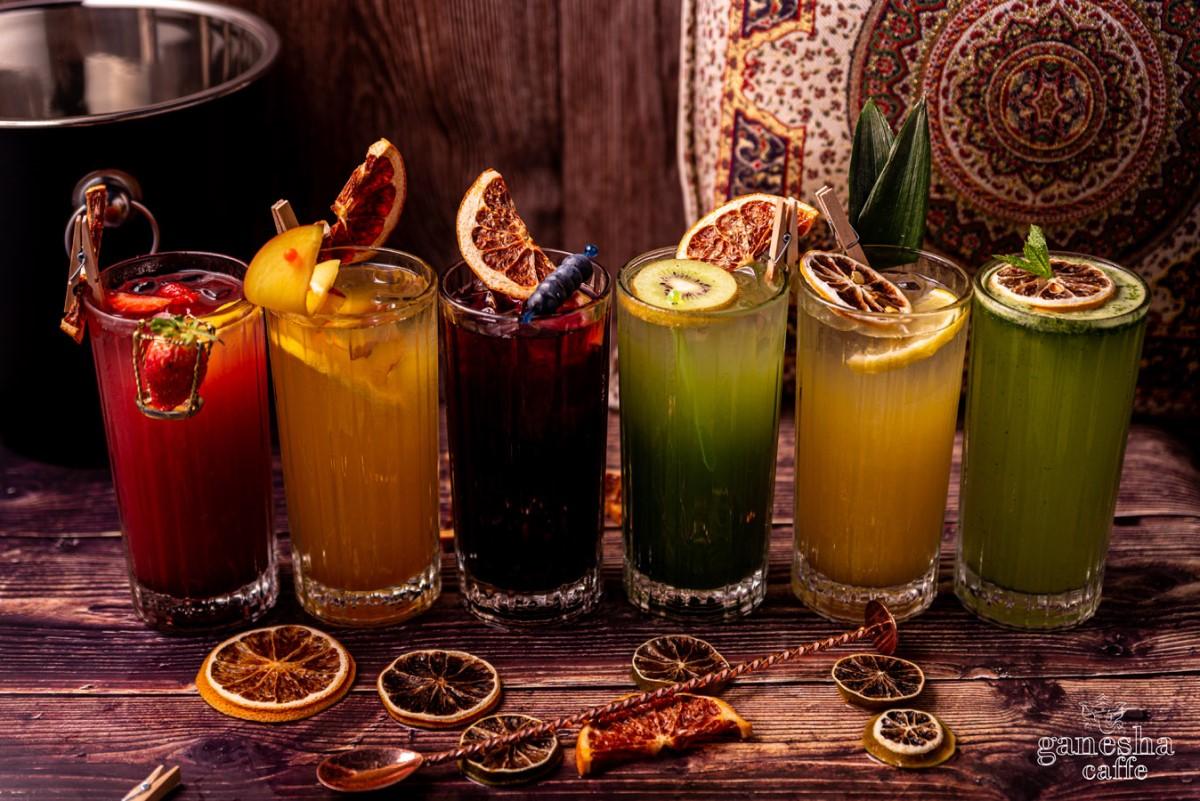6 pahare de limonada, fiecare de culori diferite, galben, verzi, rosii, portocalii, cu felii de lamaie si pai, fotografiate pe fundal maro