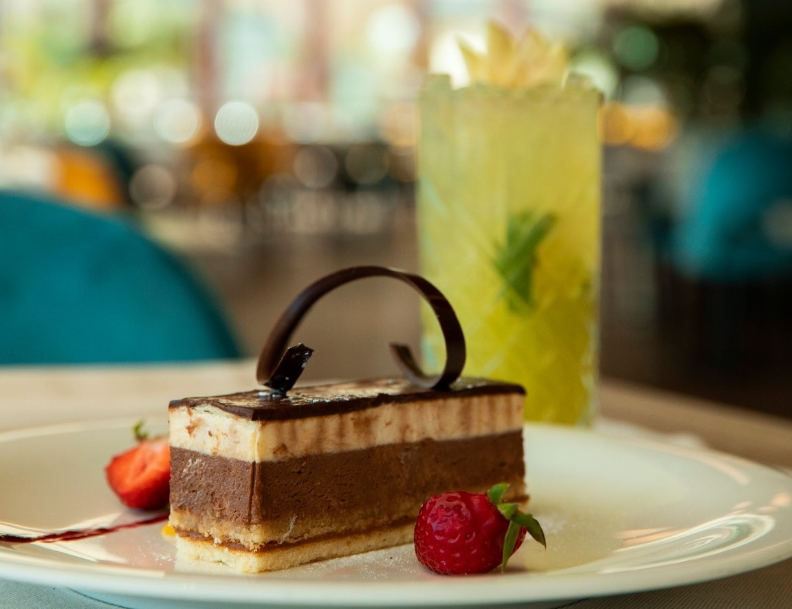 Cake cu trei straturi de ciocolata, si un decor din ciocolata, impreuna cu zmeura, la Aria TNB din București