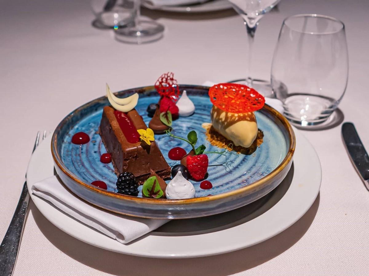 tartă de ciocolată și praline, bezea de căpșune cu yuzu, pe o farfurie albastra, la restaurant Diplomat