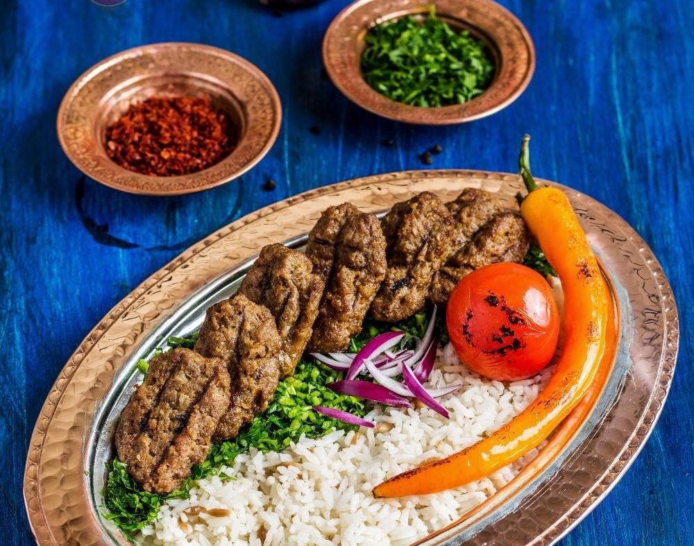 Izgara_kofte de la Efes Turkish Cuisine Concept, servit pe o tava de alama, ciu orez, rosii si ardei, si doua boluri cu patrunjel si sos. Una din mancarea ce trebuie să mănânci în Turcia.