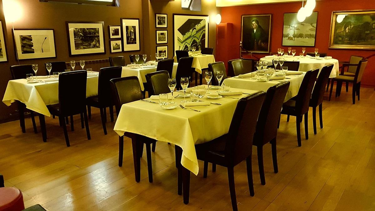 sala restaurantului La Cave de Bucarest, unul din restaurante franțuzești din București, cu mese cu fete de masa alba, scaune din piele maro, si peretii plin de tablouri alb negru.