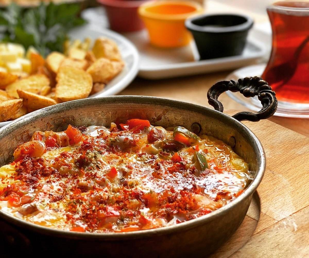 Menemen in tigaie de tabla, scoasa din cuptor, pe fundal cu cartofi prajiti si pahar de ceai, o mâncare ce să mănânci în Turcia