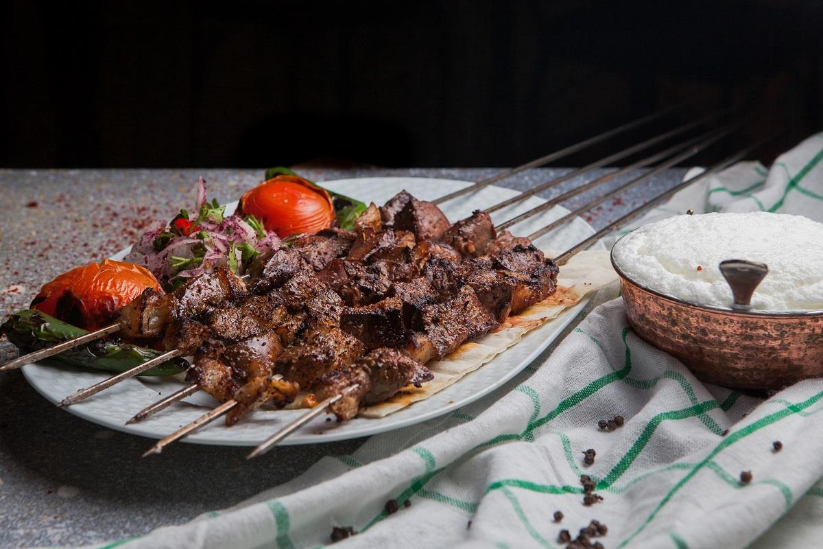 Shish kebab pe frigarui, cu rosii si ceapa si ayran, in farfurie alba pe fundal ca de piatra, un fel de mâncare se să mînânci în Turcia