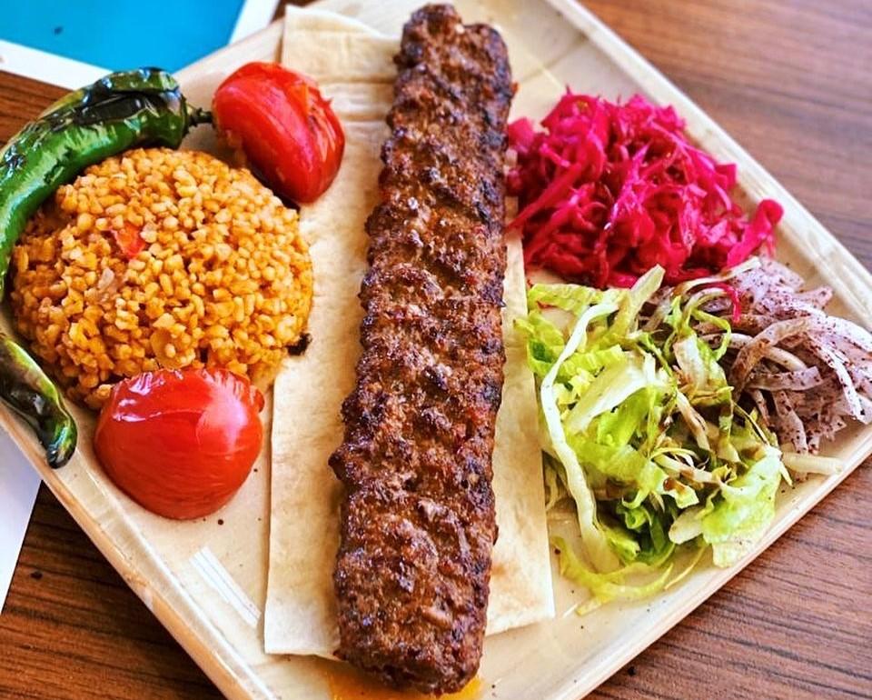 adana kebab pe farfurie alba, alaturi de pilaf cu bulgur, rosii, sfecla si salata
