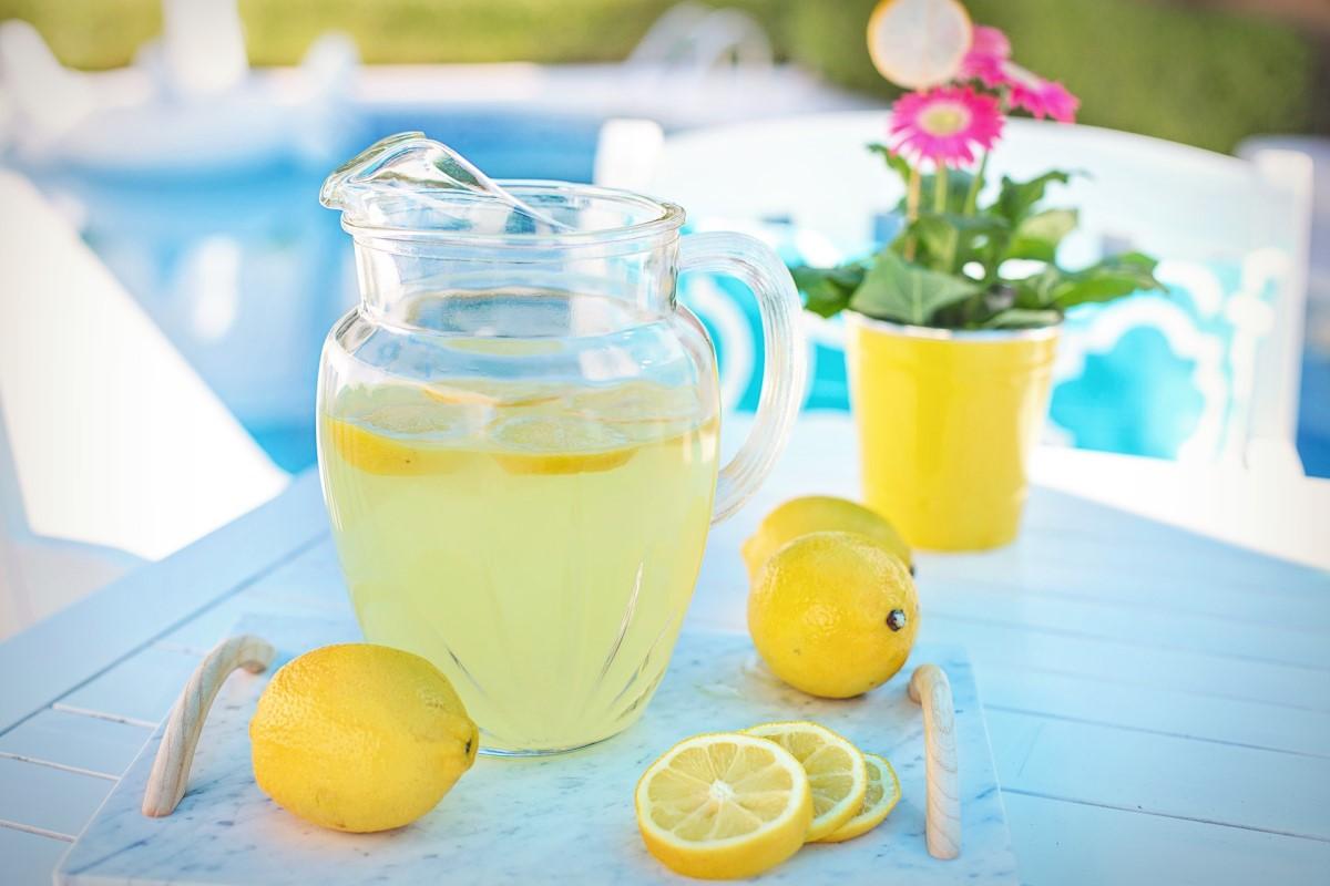 carafa cu limonada asezata pe masa, pe langa o lamaie si felii de lamaie si un ghiveci galben cu floare roz