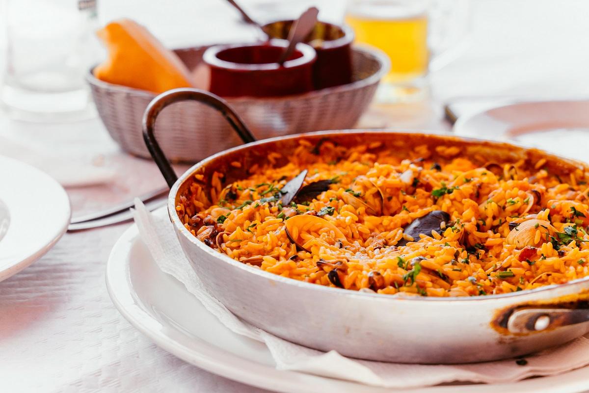 Paella spaniola cu scoici, creveti etc intr-o tigaie metalica speciala, asezata pe o farfurie alba, la restaurant, unul din preparatele ce să mănânci în Spania