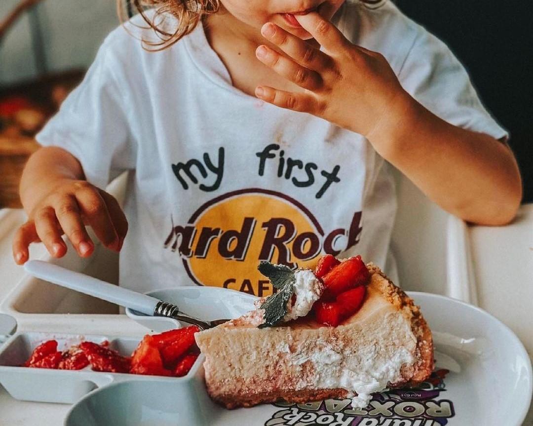 copil mic cu un tricou alb pe care scrie logoul restaurantului HArd Rock Cafe, mancand un cheesecake cu capsuni si afine, lingandu-se pe degete, la unul din restaurante si terase child friendly din București