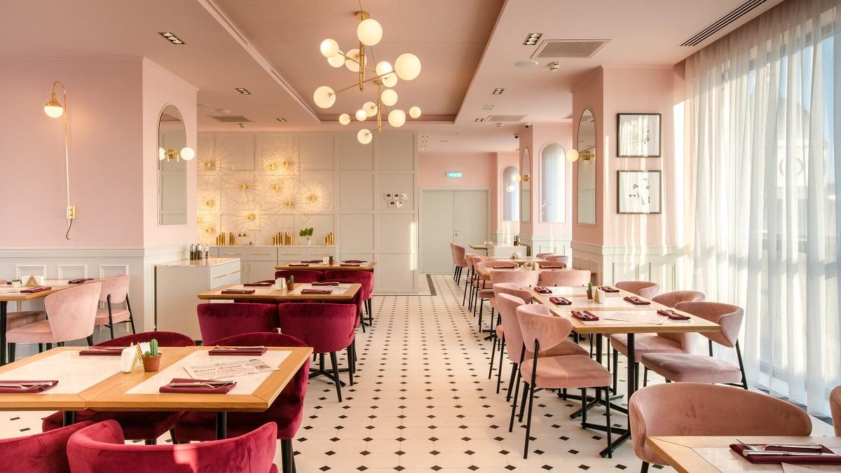 sala de mese de la restaurant Cișmigiu Bistro, cu mese asezate pe 2 randuri, scaune in nuante de roz si grena, cu mozaic alb-negru pe jos