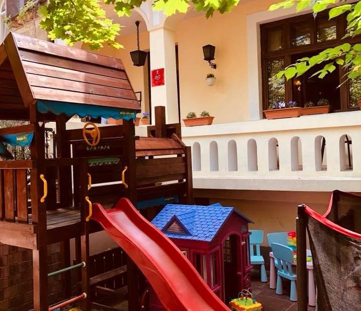 ansamblu de joaca cu casuta de lemn si tobogan la terasa Conacul Românesc Pache din București