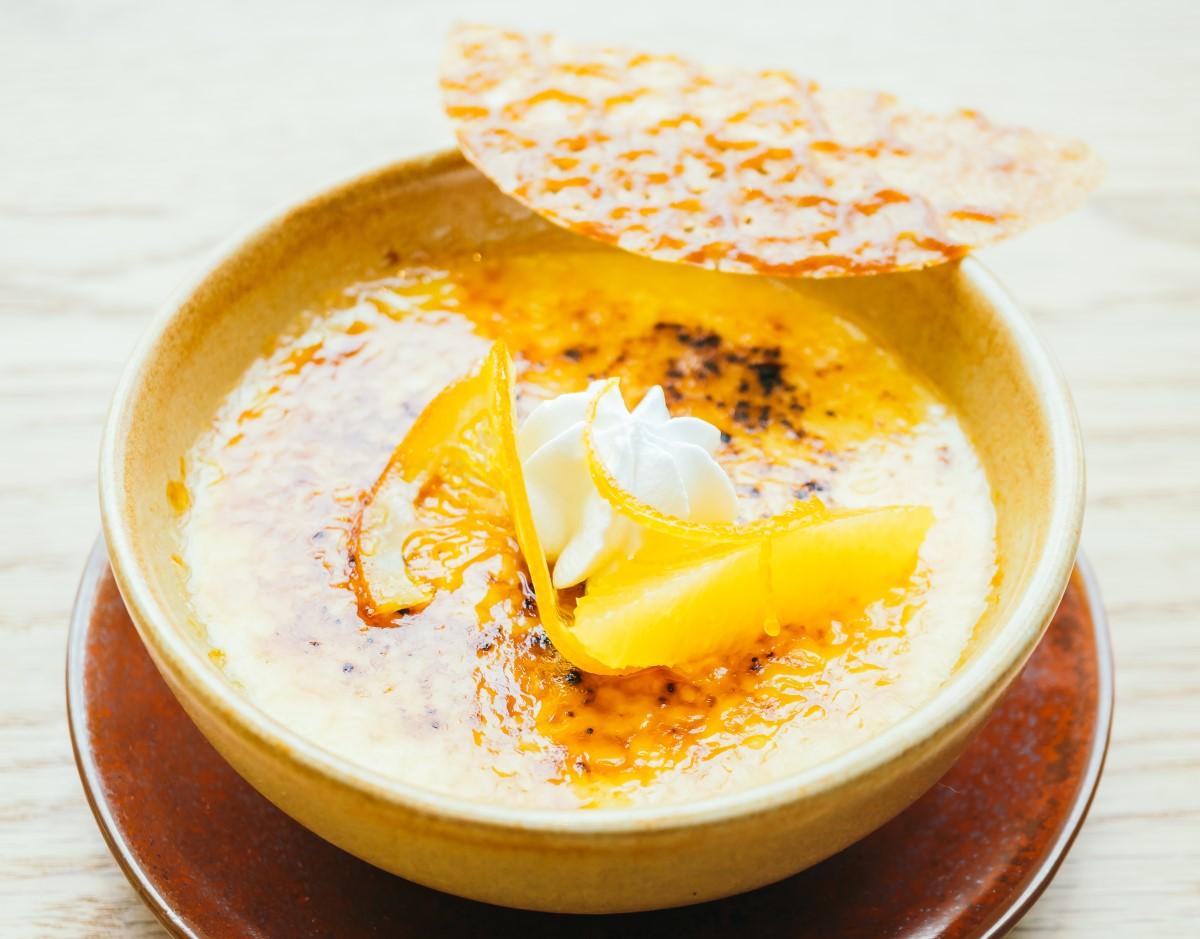 bol crem aezat pe farfurie maro, cu crema catalana decorata cu felii de portocala