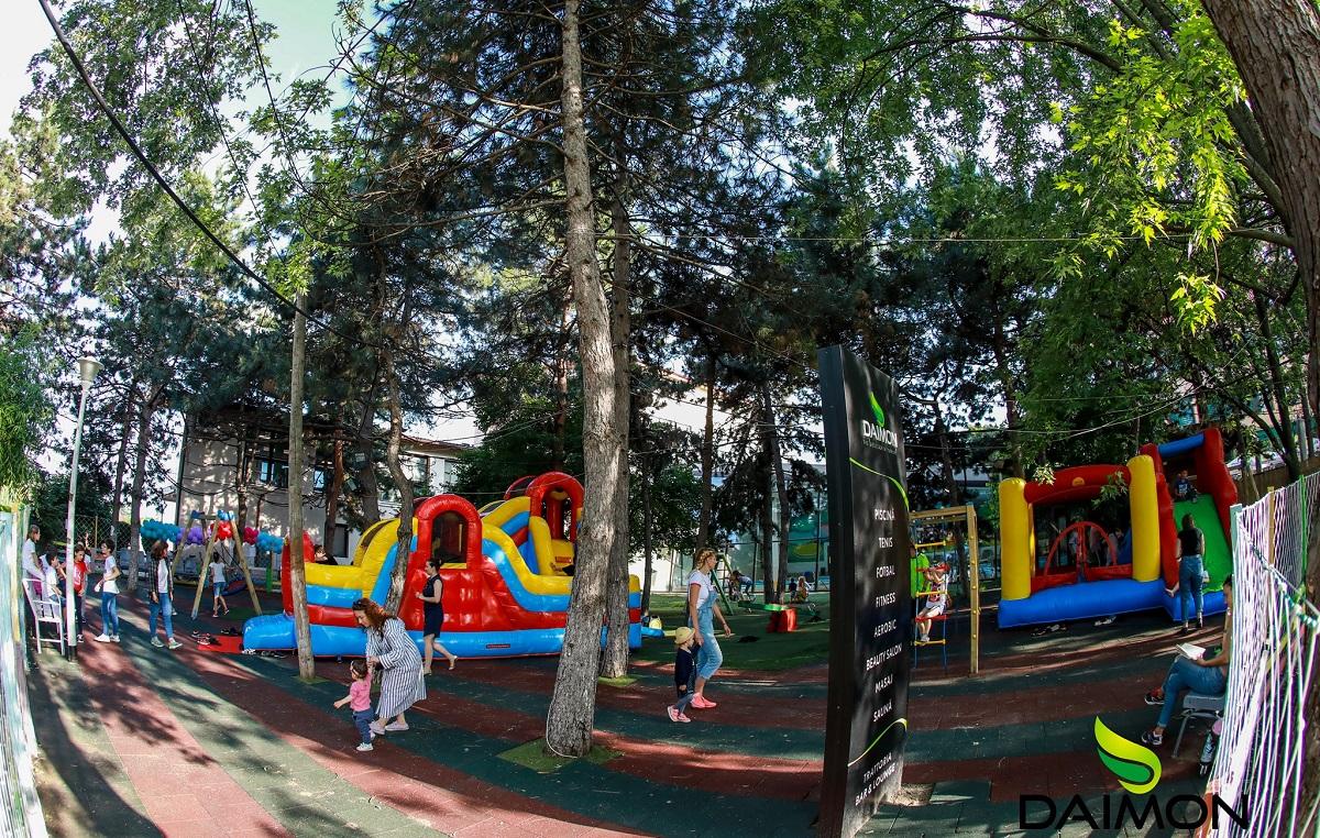 spatiu de joaca exterior de la Daimon Trattoria Social, cu tobogane gonflabile si alte elemente de joaca, printre copaci inverziti, unul din restaurnte și terase child friendly din București