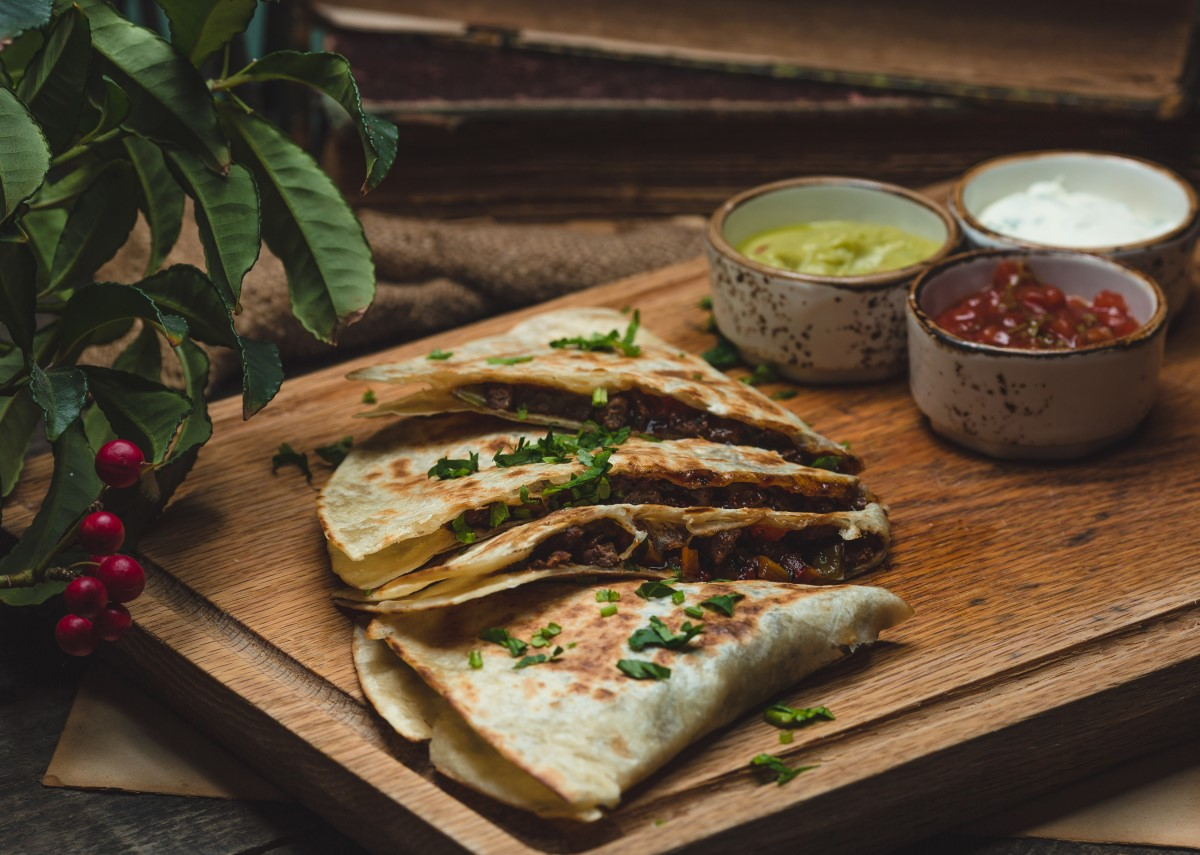 2 gozleme impaturite pe un tocator de lemnm cu boluri metalice cu sos in fundal, un snaks din cele ce să mănânci în Turcia